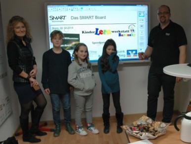 Tobias Zimmer (rechts) erklärt Petra Baronsky (von links), Marc, Lotta und Aditi das interaktive Whiteboard. Foto: Leif Kubik Zoom